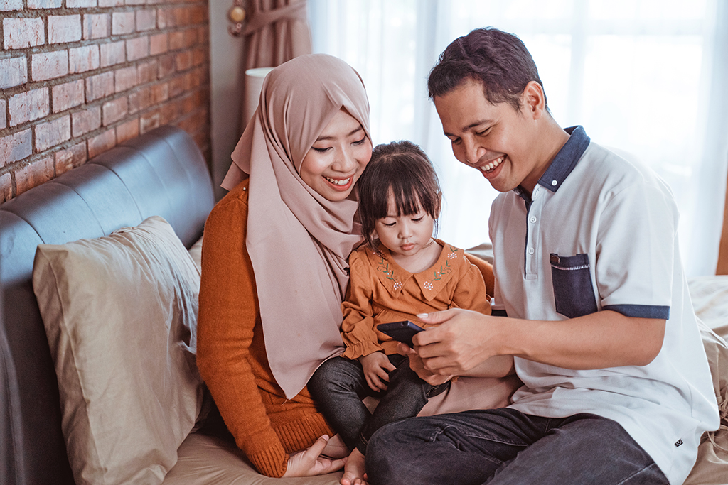 happiness of a Muslim family together when using a smartphone